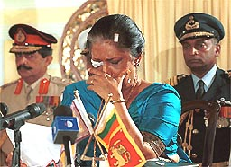 Sri Lankan President Chandrika Kumaratunga, right, is overcome by emotion at her residence in Colombo, Sri Lanka Wednesday December 22, 1999 after winning a second term in office. Kumaratunga survived a suicide bomb attack on Saturday during her final rally of the election campaign. (AP Photo/Gemunu Amarasinghe)